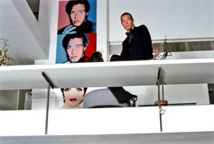 Halston seated on the ledge (second level) in the master bedroom sitting area that overlooks the living room as an open balcony. Note the three Andy Warhol silk screen canvas portraits of Halston and Liza.