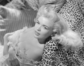 1955: American film star Jayne Mansfield reclining on some leopard-skin print cushions. (Photo by Bert Six)