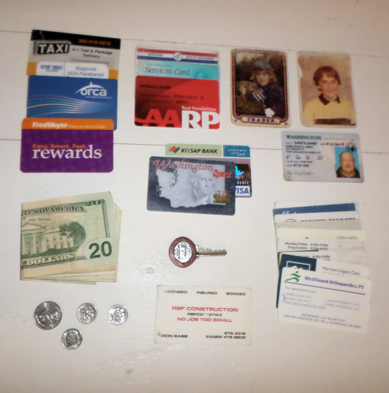 Contents of Wallet Clockwise from Upper Left:  Transit Passes, Medical Cards, Sister's Little League Baseball Card, My 9th Grade School Photograph, I.D. Card, Business Cards for Various Doctors, A Key, and $50.55.