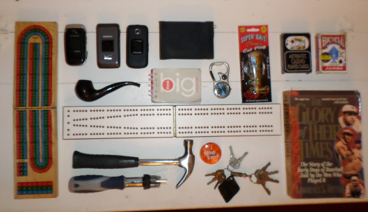Clockwise from Upper Left: Cribbage Board, Three Cellphones, Pipe, Small Notebook containing Notes and Phone Numbers, Watch/Compass, Wallet, Fishing Lure, Two Decks of Cards, Book About Baseball, Keychain I made in Cub Scouts, Reflective Light, Cribbage Board, Hammer and Multi-Head Screwdriver.
