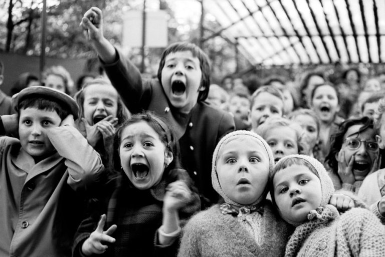 "Children watch the story of ""Saint George and the Dragon"" at an outdoor puppet theater in Paris, 1963."