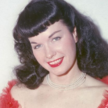 American glamour model and pin-up girl Bettie Page poses in a red negligee and stockings, circa 1955. (Photo by Archive Photos/Getty Images)